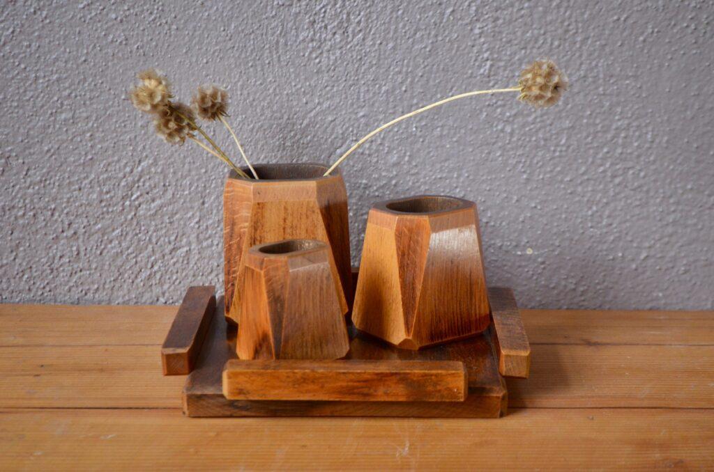 Dans un style Art Déco, ce set de bureau fait honneur au travail du bois. Trois vases de bois aux formes sobres et minimales accompagnent un plateau carré. Purement décoratif ou usuel comme set de bureau ce bel ensemble se distingue par sont élégance retenue.