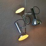 Un design de précision signe ce lustre moderniste des années soixante. En métal chromé, il est doté de 3 spots montés sur rotule et orientables. Le luminaire est minimaliste et élégant à la fois.