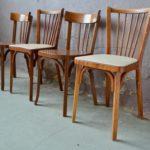 """Du skaï & du bois pour cette série de chaises Baumann vintage des années 60 emplie de générosité! Nous aimons beaucoup la douceur vitaminée qui se dégage de ce """"mix and match"""" rétro et harmonieux. Les chaises tout en bois sont dans la veine des traditionnelles chaises bistrot. Leurs lignes classiques sont relevées par une paire de chaises à l'assise gris chinée! Une belle équation qui apportera un bel esprit retro autour de la table!"""