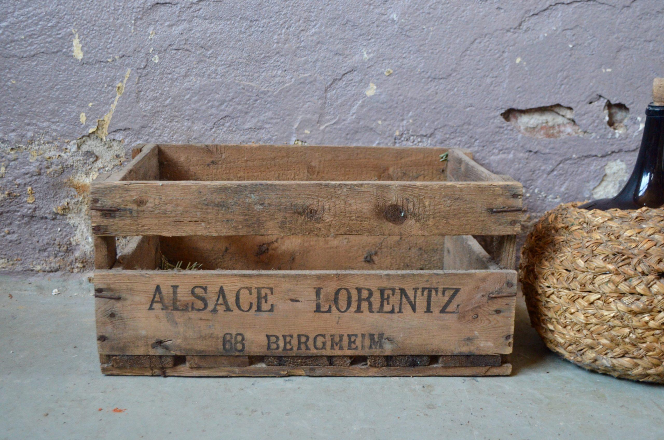 Cette caisse à bouteilles au look bohème et rustique était utilisées autrefois pour la livraison des vins dans les débits de boisson, leurs propriétaires y inscrivaient leur nom, afin de les récupérer après usage pleines de bouteilles vides! Celle ci porte le nom de Gustave Lorentz, maison de négoce reconnue installée à Bergheim au coeur de l'Alsace viticole. En bois massif, la caisse présente une patine du plus bel effet. Détournée ou pour y ranger les bouteilles, ce casier vintage apportera, en plus de son côté pratique, charme rustique et authenticité...