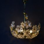 Comme un bouquet de fleur suspendu, ce lustre nous offre une ambiance délicate et bohème. Mélange de boutons floraux translucides et de tiges et feuilles en métal doré, ce lustre est une composition originale pleine de douceur.