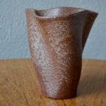 Ce vase Elchinger s'inscrit parfaitement dans les recherches formelles des créateurs midcentury. Sa forme libérée de toute contrainte ou référence s'épanouit en volutes, comme de souples drapés.Cette céramique présente un travail rare de l'émail chez les Elchinger. Il est en effet dans un registre brun, tacheté et présente un étonnant aspect granité et texturé.