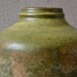 """""""Carstens Tönnieshof"""" fait partie des fabriques de céramiques allemandes qui fleurirent durant les trente glorieuses. Elle est réputée pour sa production de vases colorées aux émaux épais dans l'esprit fat lava. Ce vase au glacis épais vert texturé sur un fond noir mat et profond, au traitement brutaliste et à la forme généreuse rayonne de par sa présence massive. De belle dimension, la céramique vintage saura se mettre en valeur sur une jolie pièce de mobilier rétro."""