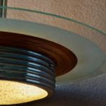 Ce plafonnier des années 30 possède un design tout en sobriété et une élégance rafinée. Comme souvent dans les productions art déco, le mélange des matières est mis en scène : Ici le métal se décline en reflets dorés et argentés alors que le verre multiplie les textures et les transparences.